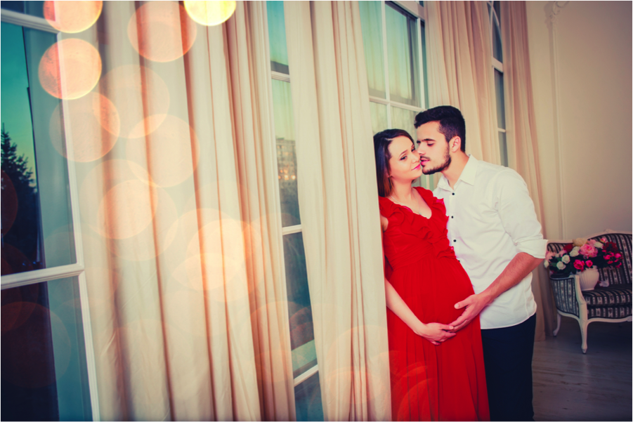 man kissing pregnant wife in front of windows